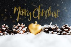 Christmas greeting card with golden heart shaped christmas tree ornament and pine cones. Snowy winter christmas greeting card with golden heart shaped christmas Royalty Free Stock Photo