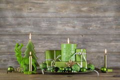 Christmas greeting card in green color. Decoration with candles. And presents on wooden background Stock Photo