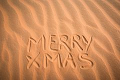 Christmas greeting card: handwritten MERRY XMAS in sand background pattern. Royalty Free Stock Photo