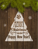 Christmas Greeting Card. Inscription with Christmas and new year 2017 against wooden texture and branches of a New Years tree Christmas Stock Photos