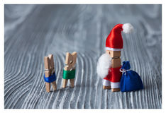 Christmas greeting card invitation. Clothespins. Santa Claus with kids and gifts. Stock Image