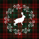 Christmas greeting card, invitation. White rabbit or hare and  Christmas wreath made of mistletoe. Tartan checkered plaid, Stock Image