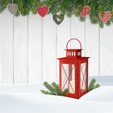 Christmas greeting card, invitation. Winter scene, red lantern with candle, Christmas tree branches, twigs. Wooden background. Stock Images