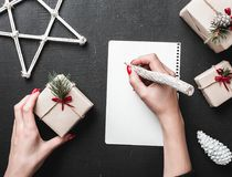 Christmas greeting card, a lady writes the gift list she will give. The Xmas ambience is supplemented by the plenty of. Christmas greeting card, a lady writes Royalty Free Stock Image