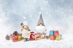 Christmas greeting card. Noel gnomes, small gifts, snow texture. Stock Photo