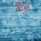 Christmas greeting card on old azure wood background. Merry Christmas inscription. Top view stock photography