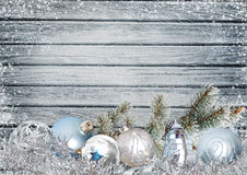 Christmas greeting card with pine branches and Christmas balls. Pine branch and Christmas balls on a snowy blue wooden background Royalty Free Stock Photo