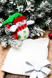 Christmas Greeting card with red ball and christmas tree, snowman on wooden background. Top view. Stock Photos