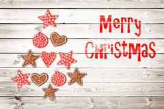 Christmas greeting card, rustic ornaments on wood planks background in the shape of a Christmas tree Royalty Free Stock Image