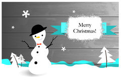 Christmas greeting card. With snowman, fir trees, on wooden background Royalty Free Stock Photography