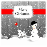 Christmas greeting card. With snowman, fir trees, on wooden background Royalty Free Stock Photos