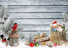 Christmas greeting card with space for text, with gifts, a lantern, a bullfinch, a bag of letters and sweets on a snowy wooden boa. Gifts, a lantern, a bullfinch Stock Photo