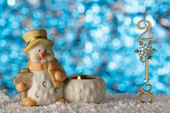 Christmas greeting card, statuette of a Snowman. 2018 the number. S in a column. The snow drifts Stock Photography