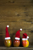 Christmas greeting card with three red santa hats on apples with Stock Images