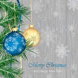 Christmas  greeting card on a wooden texture. Christmas baubles, snowflakes and needles. Royalty Free Stock Image