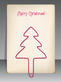 Christmas greeting with christmas tree shaped paper clip Stock Photos