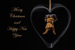 Christmas greeting with dancing straw dolls in a heart. Christmas greetings with dancing straw dolls in a rotating metal heart and with the text: Merry Christmas Stock Photography