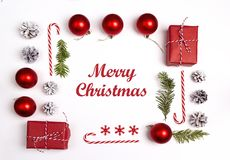 Christmas greeting message with decorations and gifts on white background. Flat Lay stock images
