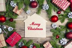 Christmas greeting message on home symbol with Christmas fir branches, presents and decorations on old wooden table royalty free stock image