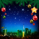 Christmas greeting with pine branch and panorama of city Stock Photo