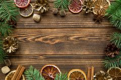 Christmas background, free space for text. Christmas greeting table background. Dried sicilian oranges, golden fir cones, spices, like anise and cinnamon sticks stock photos