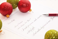 Christmas greetings. With Red glitter balls in background Stock Image