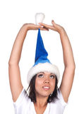 Christmas growing up. Young woman pulling herself up by Christmas hat Stock Images