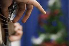 Christmas Guitar. Hands playing acoustic guitar, Christmas tree in the background.  Focus on hand in foreground, shallow depth of field Royalty Free Stock Photos