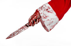 Christmas and Halloween theme: Santa's bloody hands of a madman holding a bloody knife on an isolated white background Royalty Free Stock Photos