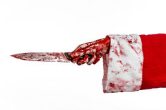Christmas and Halloween theme: Santa's bloody hands of a madman holding a bloody knife on an isolated white background Stock Image