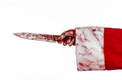 Christmas and Halloween theme: Santa's bloody hands of a madman holding a bloody knife on an isolated white background Stock Photos
