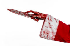 Christmas and Halloween theme: Santa's bloody hands of a madman holding a bloody knife on an isolated white background Stock Images