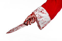 Christmas and Halloween theme: Santa's bloody hands of a madman holding a bloody knife on an isolated white background Royalty Free Stock Images