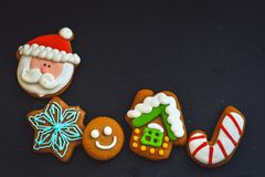Christmas cookies. Christmas hand decorated smile cookies cinnamon on black slate dark moody of decorative food, simple composition royalty free stock image