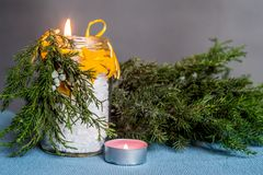 Christmas hand made candle craft on the blue tablecloth with a fir tree spruce and a candle Stock Photo