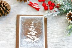 Christmas. Hand made christmas card, heart and cones  on wooden background Stock Photo