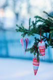 Christmas handmade blue and red fabric heart decorations with fir branches in snowy winter, selective focus Stock Photo