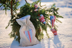 Christmas handmade blue and red fabric heart decorations and gift bag with fir branches in snowy winter, selective focus Stock Photos
