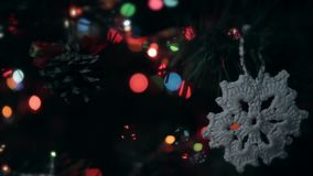 Christmas handmade decoration a cone and a crocheted snowflake. Lights flash stock video