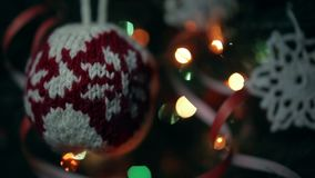 Christmas handmade decoration a knitted ball and a crocheted snowflake. Lights flash stock video