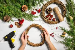 Christmas handmade diy background. Making craft xmas wreath and ornaments. Top view of white wooden table with female stock photography