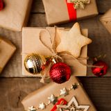 Christmas handmade gift box decorated with craft paper and red gold balls and handmade cookie star on vintage wooden background to royalty free stock photos