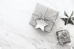 Christmas handmade gift boxes on white marble background top view. Merry Christmas greeting card, frame. Winter xmas holiday theme. Christmas silver handmade stock photography