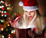 Christmas. Happy Blonde Girl with Santa Hat Opening Gift Box. Over lights of Christmas tree. Miracle Stock Image