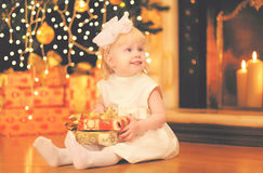 Christmas happy child little girl with gift box near christmas tree and fireplace home Royalty Free Stock Image