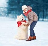 Christmas happy child walking with white Samoyed dog in winter royalty free stock images