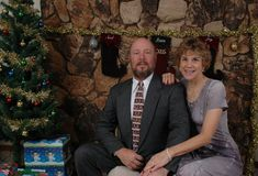 Christmas with the Happy Couple. Husband and wife in front of the Christmas Tree with presents under it Stock Photography
