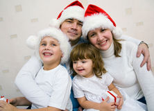 Christmas Happy family. The happy family with two small children in Christmas caps rejoices together Stock Photos