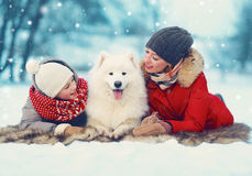 Christmas happy family, mother and son child walking with white Samoyed dog, lying on snow in winter day. Flying snowflakes stock photos