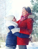 Christmas happy family, son child hugs his mother in winter sunny day Royalty Free Stock Photos